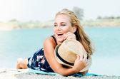 Mosolygó fiatal nő kalapot a strandon