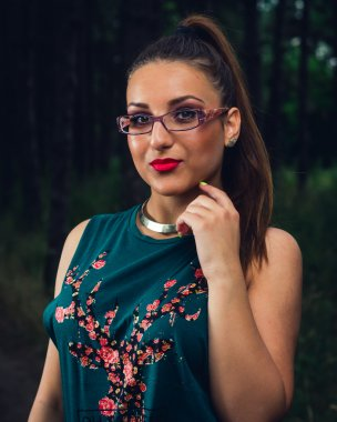Portrait of young,  elegant woman with glasses in the forest