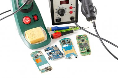 Group of mobile phones with soldering guns and screwdriver