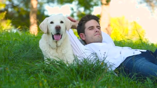 young man lying with his old senior labrador dog in the meadow