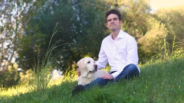 young man petting white labrador dog