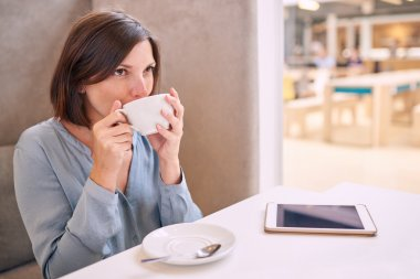 casual well dressed woman taking a sip of her coffee