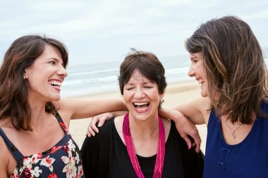 Mother and daughters laughing happily togehter on the beach