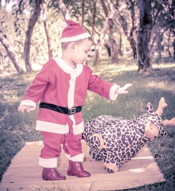 A kid in Santaclaus suit push reindeer doll away , unfriend conc