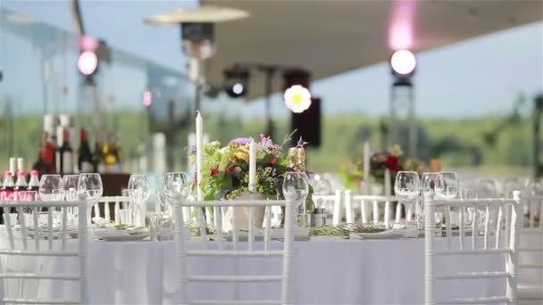 Glasses on white cloth table served for lunch or dinner in luxurious outdoor terrace restaurant with cozy interior