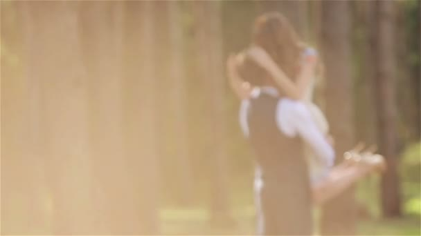 Man holding woman with his hands aweigh in nature. Woman caressing hair of man touching head and kissing him on a date in a forest