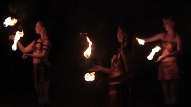 Fire show performance. Group of hot women female fire performers dance gathering up burning fire torches on black background. Slow motion