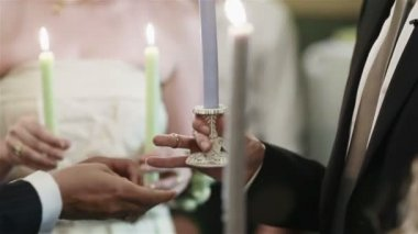 Closeup view of the priest hands putting the wedding rings on the