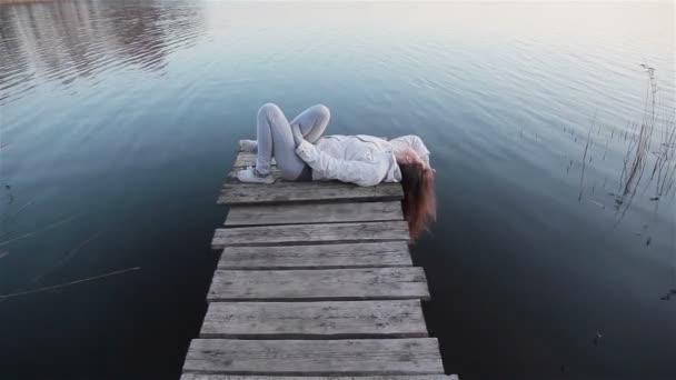 Mladá žena ležící na dřevěném molu uvolňující a dotýká její vlasy převis na jezero vody
