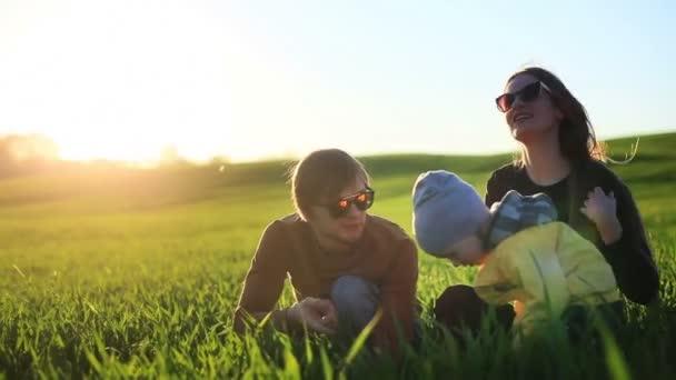 Mladí rodiče a jejich malý syn sedí v zelené trávě, baví a mluví v letním parku venku v přírodě. Otec ukazující a něco vysvětlovat syna