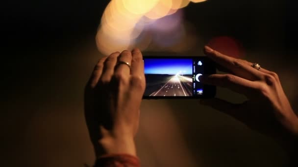 Close up of female hands holding smart phone and pushing button taking pictures of empty night road with no traffic with beautiful blurry lights bokeh background