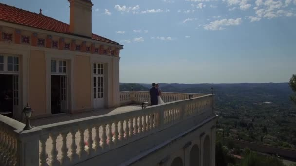 Man and woman stand embracing on balcony view from above flyover. Couple in love have romantic date at ancient house terrace with mountains view at background Europe France. Wedding day destination