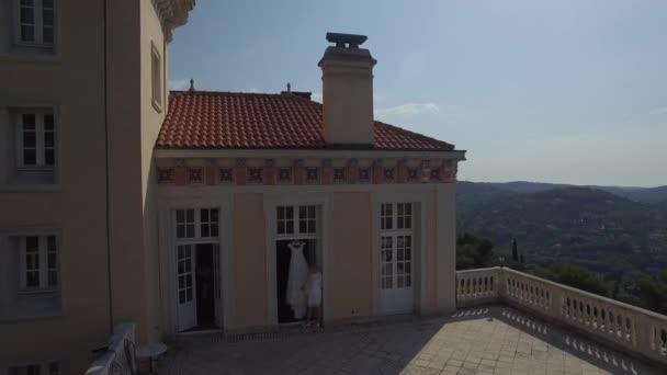 Brautkleid auf der Terrasse. Braut berühren Hochzeitskleid auf dem Balkon des alten Schlosses in Europe France Grasse Mountain Area hängen. Hochzeitsagentur plant Tagesvorbereitungen. Drohnen-Hubschrauber überfliegen