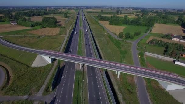 Fliegen Sie über Überführung Brücke am Highway in Landschaft mit PKW-LKW-LKW bewegt beide Richtungen 4k HD-Ansicht von oben. Multiplizieren Sie Lane aufgeteilt Fahrbahn Fahrzeuge Verkehr am sonnigen Tag in Polen-Ost-Europa