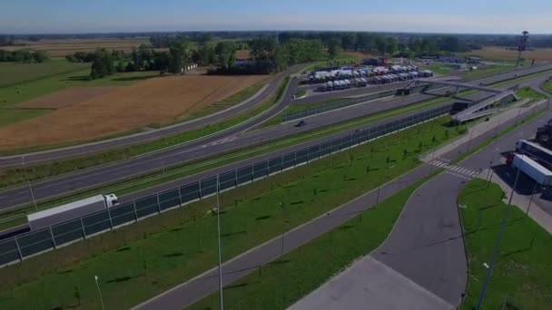 Gas filling station and truck lorries parking on both sides of highway road with pedestrian overpass bridge above connecting them aerial top view 4K HD copter video. Drivers working hours regulations