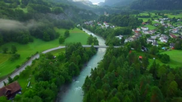 Mountain river bridge with car moving in countryside 4k aerial top view. Drone flight over road fields houses idyllic view of Swiss village green trees castle. Quality of life real estate and tourism