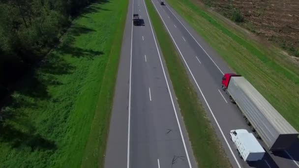 Highway aerial with cars and truck lorry moving aerial view 4k. Four lane local road traffic transport vehicles driving both directions bird eye top above