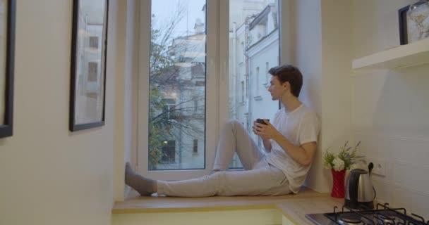 Vergrößern Sie das Porträt eines nachdenklichen Mannes, der Tee trinkt, in Zeitlupe. Seitenansicht eines Jungen, der auf der Fensterbank sitzt und an das Leben im Innenraum denkt. Konzept Isolationsquarantäne bleibt zu Hause