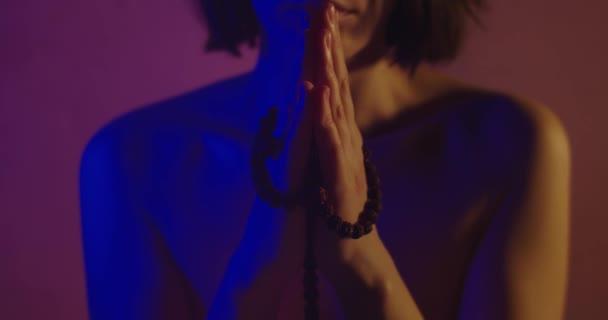 Nahá dívka modlící se v neonovém světle. Žádná nahá dívka s obličejem, modlící se ozářená neonovým světlem. Mladá sexy žena bez oblečení drží růženec v rukou a čte modlitbu. Víra a spiritualita