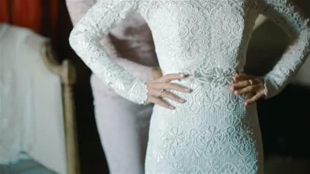 Nevěsta se dotkne její krajkové svatební šaty s její krásné pěstěné prsty