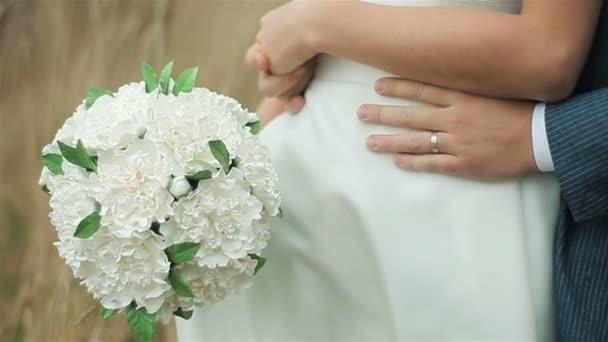 Groom hugging bride holding wedding bouquet. Close-up