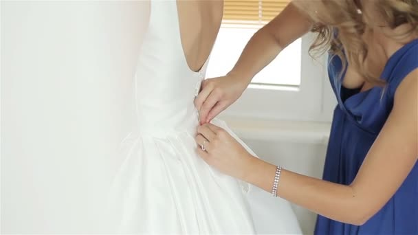 Bridesmaid helping Bride to button wedding dress