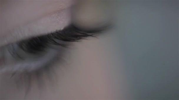 Maskérka použití falešných řas na oku modelu. Zblízka, makro