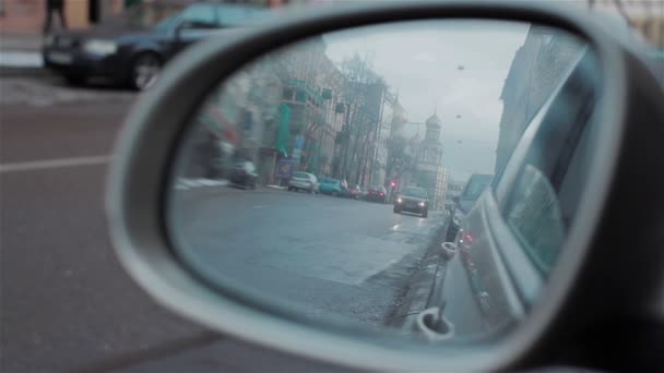 Back road reflected in car mirror, evening street with buildings and moving cars. Car with headlights on turning