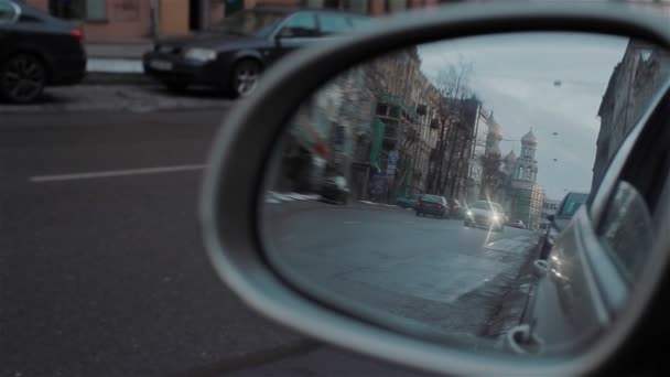Back road reflected in car mirror, evening street with buildings and moving cars. Car with headlights on passing by