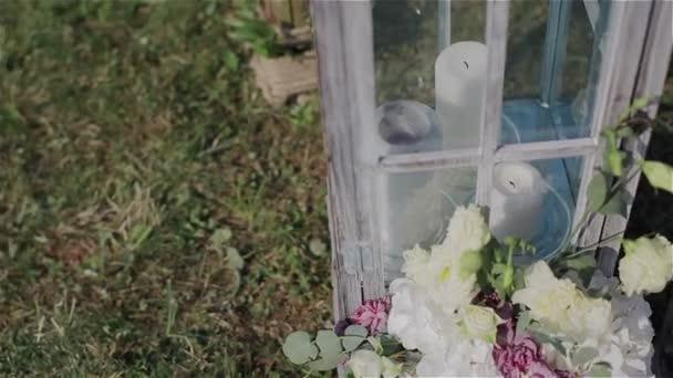 Esküvői dekoráció, esküvő szabadban. Fehér gyertya és virág a kertben. Közelről. Pán lövés
