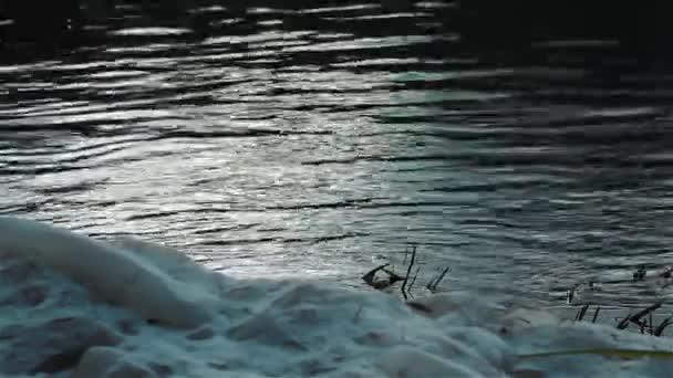 Zasněžený břeh řeky. Zblízka