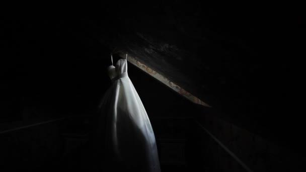 Bílé svatební šaty visí v temné místnosti. Dva výstřely