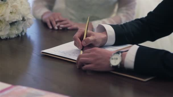 Bride and groom signing marriage certificate. Close-up