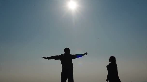 Silhouette of happy young couple embracing on a background of sky and sea. Man twirling his woman around on his hands