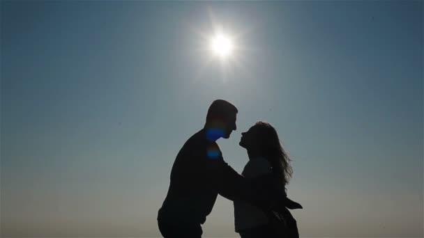 Uprostřed siluety šťastných mladých pár, kteří se líbali a drželi se za ruce na pozadí nebe a moře