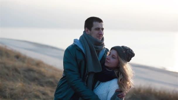 Šťastný mladý krásný usmívající se pár a jemně Neobjímej úžasný západ slunce moře pozadí
