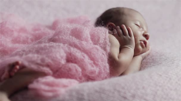 Close up of adorable little newborn baby girl sleeping on a pink knitted blanket in a lovely pose with hands pressed to cheeks