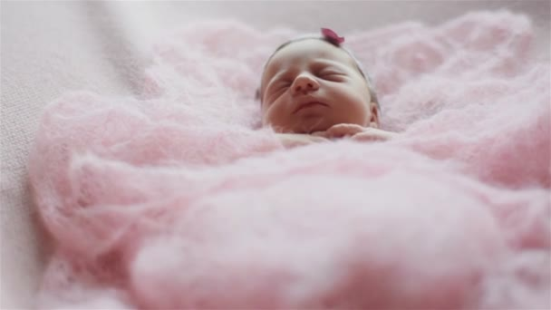 Close up of beautiful tiny newborn baby girl sleeping covered with a light pink knitted blanket