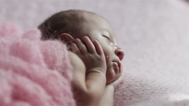 Extra close up macro of cute tiny newborn baby girl sleeping on a pink knitted blanket in a lovely pose with hands holding cheeks