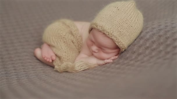 Close up of adorable little newborn baby in a knitted cap sleeping on a blanket crossing legs in a lovely pose with hands under head. Two shots in a sequence