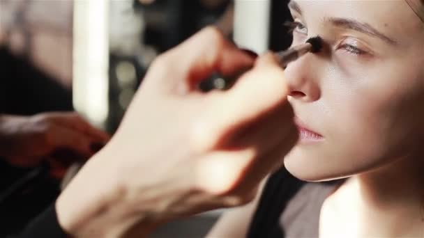Professional make-up artist applying foundation with a brush to skin of models face. Close-up