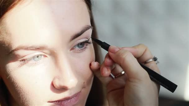 Professional make-up artist applying eyeliner. Close-up