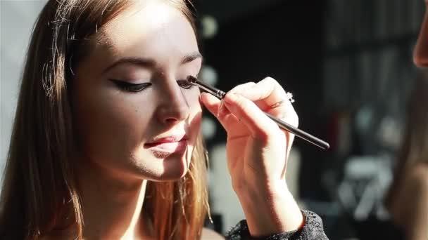 Profesionální make-up umělce používání světlé oční stíny. Detail