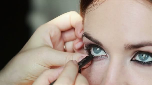 Professional make-up artist lining inner rim of the eye. Close-up
