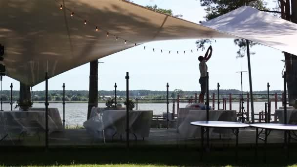 Mann arrangiert Lichterketten auf einer Sommerterrasse am See. Vorbereitungen für die Party in einem Restaurant im Freien. Dekoration für Hochzeitsempfang