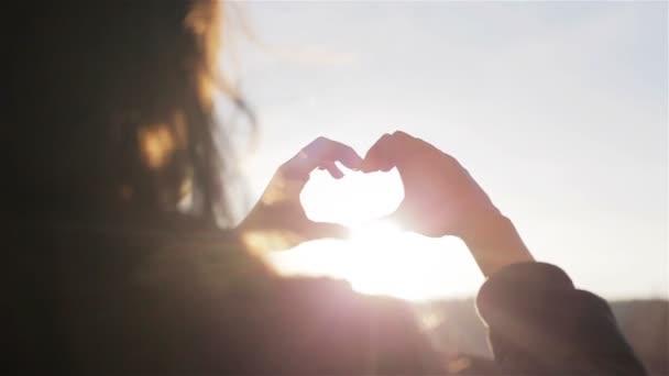 Ženské ruce srdce tvar gesto drží odlesk slunce s prsty na modré obloze