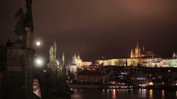 Noční panoramatické rozhledny Karlova mostu s antickým sochami nad řeky Vltavy a historické centrum Pražského hradu v dálku budov a památek starého města