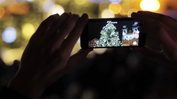 Ruce držící chytrý telefon, natáčení osvětlené tradiční vánoční strom a katedrála na Staroměstské náměstí v Praze, Česká republika. Vánoce v Evropě