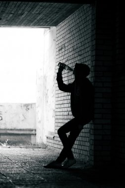 Teenager drinking beer and standing in the alley
