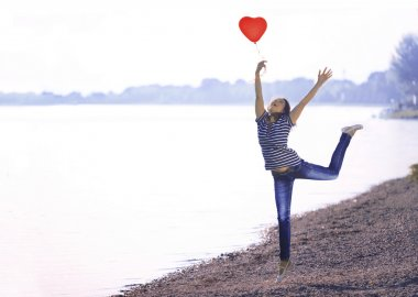 Happy Young Woman Jumping with a Shaped Heart Balloon